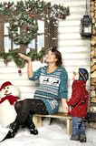 Young pregnant woman sits on a bench with the child about a snowman Royalty Free Stock Images