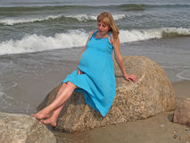 The young pregnant woman sits on a boulder on the bank of the Baltic Sea Royalty Free Stock Images