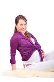 Young pregnant woman sits on white fur Stock Image