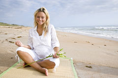 Young pregnant woman sitting on beach Stock Photo