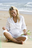 Young pregnant woman sitting on beach royalty free stock image