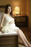 Young pregnant woman. Pregnant woman sitting on a bed and caressing her belly Royalty Free Stock Photography