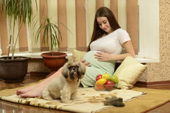 Young pregnant woman. Sitting on the carpet Stock Photo