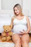 Young pregnant woman sitting on the floor with a teddy bear Royalty Free Stock Photos