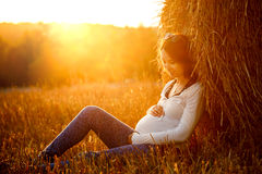 Young Pregnant Woman Sitting by the Haystack Royalty Free Stock Images