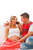 Young pregnant woman sitting with husband on couch Stock Photo