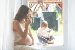Young pregnant woman, sitting indoor, watching her child through Royalty Free Stock Photo