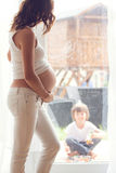 Young pregnant woman, sitting indoor, watching her child through Stock Photography