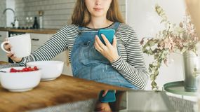 A young pregnant woman is sitting in the kitchen at the table, having breakfast, drinking tea and using a smartphone. stock photo