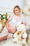 Young pregnant woman  sitting near white sofa with teddy bear Royalty Free Stock Photography