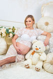 Young pregnant woman  sitting near white sofa with teddy bear Royalty Free Stock Images