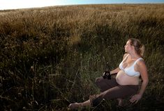 Young Pregnant Woman Sitting in an Open Field Royalty Free Stock Photo