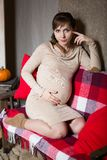 Young pregnant woman sitting on sofa Royalty Free Stock Photography