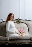 Young pregnant woman sitting on the sofa Royalty Free Stock Photos