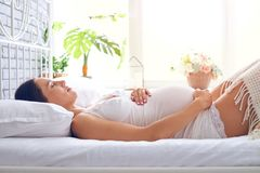 Young pregnant woman sleeping on bed in white bedroom Royalty Free Stock Photography
