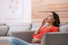 Young pregnant woman smoking cigarette at home royalty free stock image