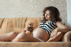 Young pregnant woman on the sofa. Young pregnant woman with a teddy bear on the sofa Royalty Free Stock Photos