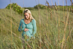 Young pregnant woman standing alone in field Stock Photo