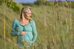 Young pregnant woman standing alone in field Stock Photography