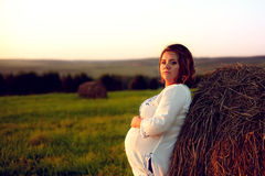 Young Pregnant Woman Standing by the Haystack at Sunset and Embr Royalty Free Stock Photo