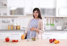 Young pregnant woman standing near table with breakfast. In kitchen Royalty Free Stock Photo