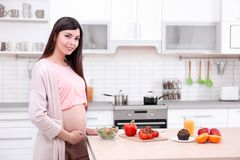 Young pregnant woman standing near table with food. In kitchen Stock Photography