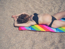 Young pregnant woman sunbathing on beach. A pregnant young woman is sunbathing on a beach Royalty Free Stock Image