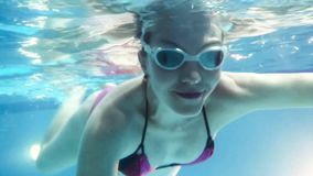 Young pregnant woman swimming underwater stock video