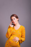 Young pregnant woman talking on mobile phone. Portrait of young pregnant woman talking on mobile phone royalty free stock photo