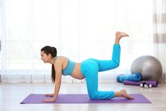 Young pregnant woman training in gym. stock photos
