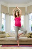 Young pregnant woman in tree pose yoga stance in living room, portrait Stock Photo