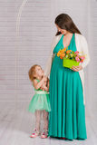 Young pregnant woman in a turquoise dress Royalty Free Stock Photos