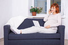 Young pregnant woman using laptop and talking by phone in living Royalty Free Stock Images