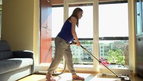 Young pregnant woman vacuuming floor in front of window stock video footage
