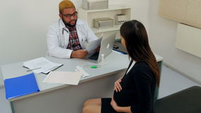 Young pregnant woman visiting physician and giving him some medical papers stock video footage
