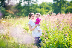 Young pregnant woman walking with her little daughter Stock Photos