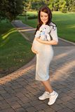 A young pregnant woman walking holding teddy bear toy in the park stock photos