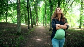 Young pregnant woman walking at summer park among tree alley stock video
