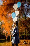 Young pregnant woman walks in autumn park. With balloons in hand stock images