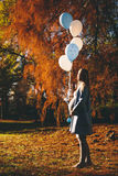 Young pregnant woman walks in autumn park. With balloons in hand stock photo