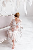 Young pregnant woman wearing lace dress in white interior. Fashion shot. Royalty Free Stock Photos