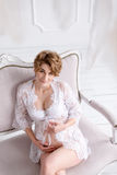 Young pregnant woman wearing lace dress in white interior. Fashion shot. Stock Images
