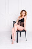 Young pregnant woman wearing lace lingerie in white interior. Fashion shot. Stock Photo