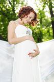 Young pregnant woman in white dress. In the garden Royalty Free Stock Photography