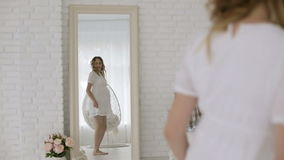 Young pregnant woman in a white dress having fun dancing in front of a mirror.