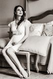 Young pregnant woman in white dress sitting royalty free stock photos