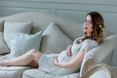 Young pregnant woman in white dress sitting. In one of rooms in mansion royalty free stock photos