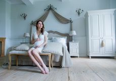 Young pregnant woman in white dress sitting royalty free stock image