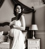 Young pregnant woman in white dress royalty free stock image