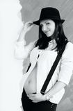 Young pregnant woman in white shirt with suspenders and hat Royalty Free Stock Image